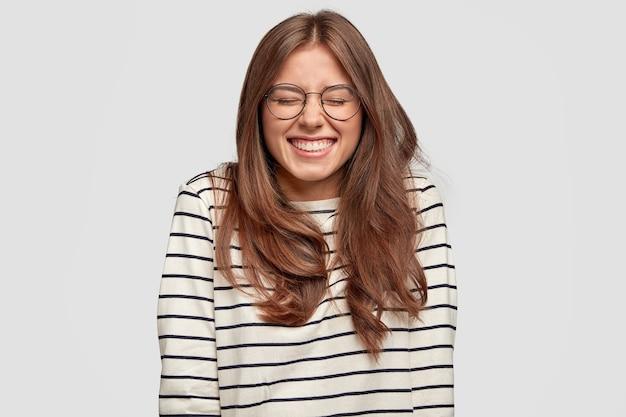 Pozytywna optymistka młoda kobieta uśmiecha się radośnie, ma równe białe zęby, ubrana swobodnie, będąc w dobrym nastroju, wyraża radość, spędza wolny czas z przyjaciółmi, odizolowana na białej ścianie