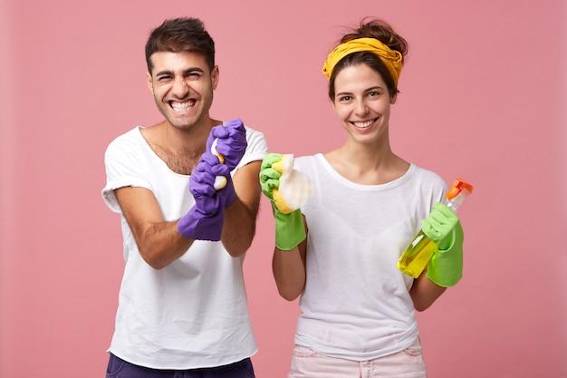 Pozytywna para robi prace domowe: stylowy mężczyzna w ochronnych rękawiczkach trzyma gąbkę i uśmiechnięta gospodyni domowa trzyma szmatkę z sprayem, stojąc razem odizolowani na różowej ścianie. prace domowe, koncepcja czyszczenia