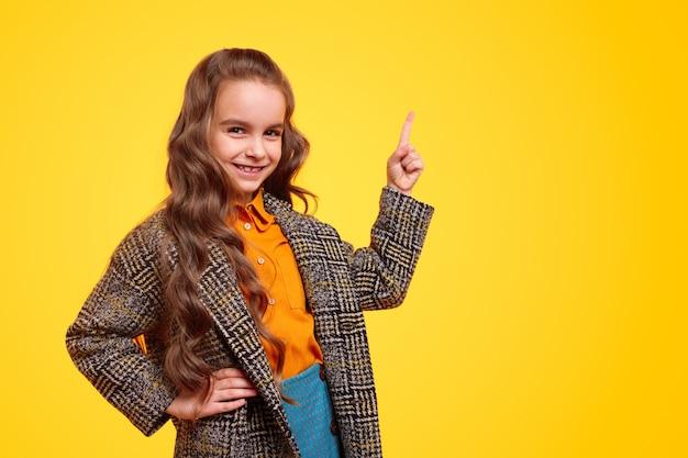 Pozytywna pewna siebie dziewczyna w stylowy płaszcz dorywczo, trzymając rękę w talii i skierowaną w górę