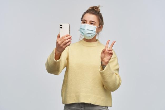 Pozytywna, piękna dziewczyna o blond włosach zebranych w kok. noszenie żółtego swetra i ochronnej maski na twarz. robienie selfie na smartfonie i pokazanie znaku pokoju. stań na białym tle nad białą ścianą