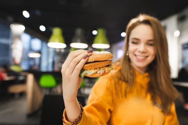 Pozytywna piękna dziewczyna siedzi w fast food restauraci