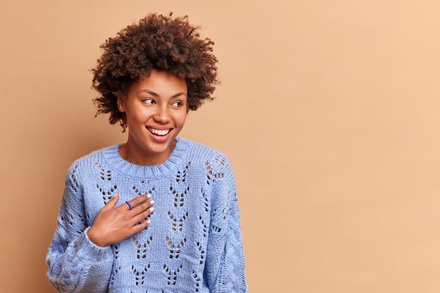 Pozytywna piękna kobieta uśmiecha się delikatnie i cieszy się radosną rozmową z kimś skoncentrowanym na boku szczęśliwie ubranym w sweter z dzianiny odizolowany na beżowej ścianie w obszarze kopii