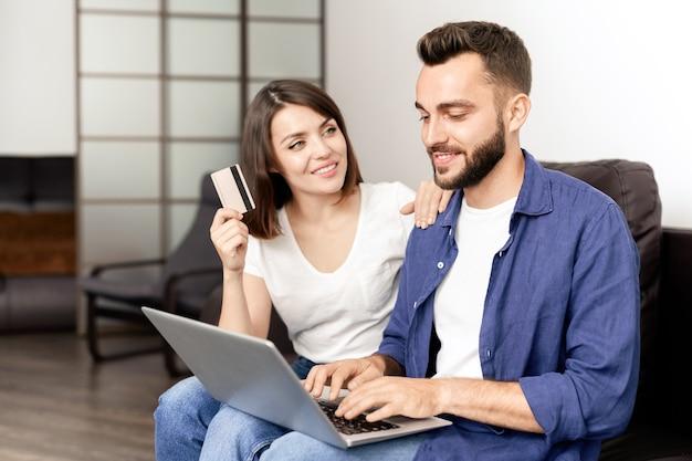 Pozytywna piękna para w zwykłym ubraniu siedzi na kanapie w domu i korzysta z laptopa podczas kupowania mebli w internecie