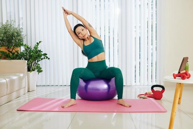 Pozytywna piękna sprawna młoda kobieta siedzi na piłce fitness i robi boczne skłony z rękami nad głową