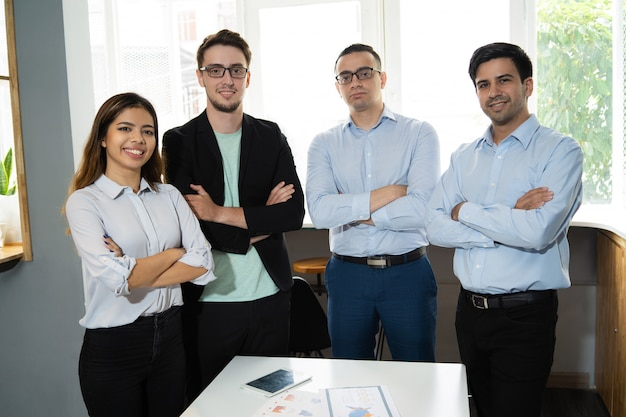 Pozytywna pomyślna biznes drużyna pozuje przy miejscem pracy