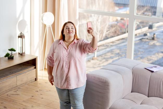 Pozytywna, pulchna kobieta uśmiecha się do kamery podczas robienia selfie