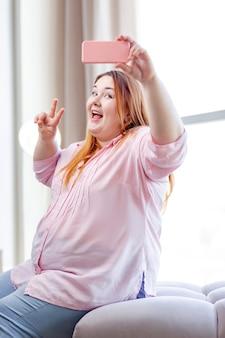 Pozytywna, pulchna kobieta uśmiecha się, pozując do selfie