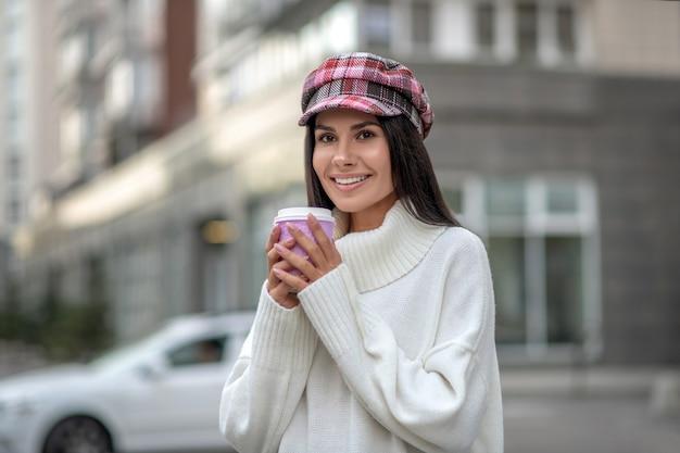 Pozytywna radosna kobieta uśmiecha się trzymając kubek z kawą