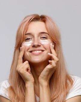 Pozytywna radosna młoda kobieta stosuje nawilżający liftingujący krem odżywczy na dzień lub zabieg na twarz
