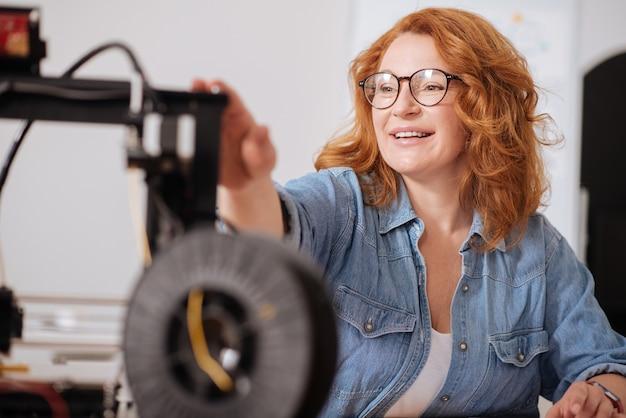 Pozytywna radosna rudowłosa kobieta dotyka drukarki 3d i uśmiecha się siedząc przy stole