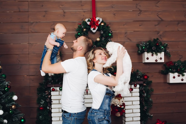Pozytywna rodzina pozowanie razem przy kominku i prezenty na boże narodzenie
