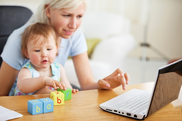 Pozytywna rodzina za pomocą laptopa i zabawy z zabawkami