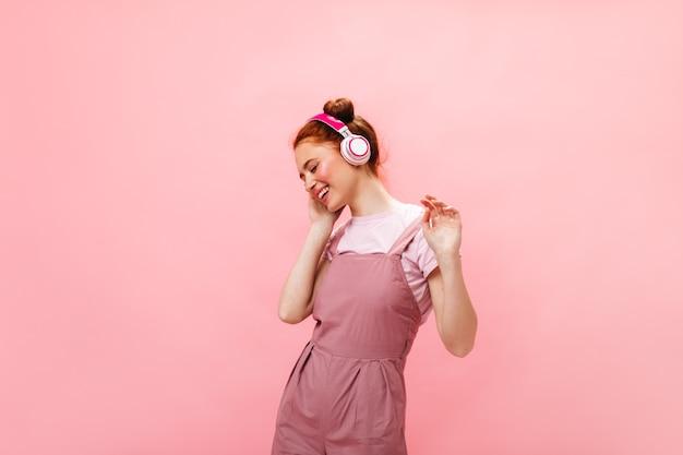 Pozytywna ruda dama w różowym stroju śmieje się podczas słuchania muzyki z różowymi słuchawkami na na białym tle.