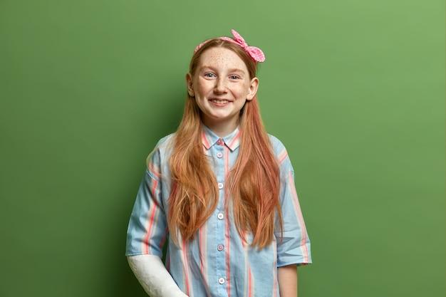 Pozytywna ruda dziewczyna o piegowatej twarzy, ma radosny wyraz twarzy, nosi opaskę i koszulę, wyraża radość, ma złamaną rękę, lubi spotkania z przyjaciółmi, izolowana na zielonej ścianie, bycie w dobrym nastroju