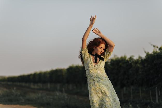 Pozytywna rudowłosa dama z czarnym bandażem na szyi w zielonych letnich ubraniach uśmiecha się i pozuje z rękami w górze na winnicach