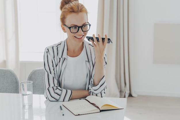 Pozytywna rudowłosa kobieta używa rozpoznawania dźwięku telefonu komórkowego do wysyłania wiadomości