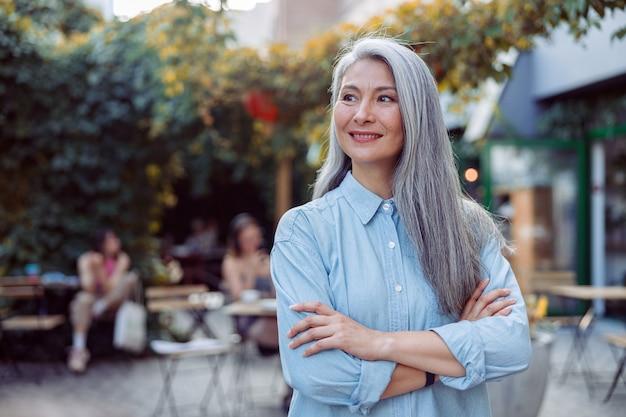 Pozytywna siwowłosa azjatycka dama ze skrzyżowanymi rękami na tarasie kawiarni na świeżym powietrzu