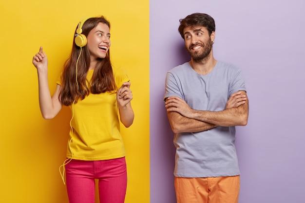 Pozytywna śliczna kobieta tańczy i słucha muzyki w słuchawkach, szczęśliwy mężczyzna z założonymi rękami patrzy na dziewczynę, będąc w dobrym nastroju