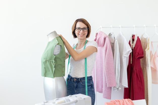 Pozytywna śliczna uśmiechnięta młoda krawcowa kobieta w okularach z miarką dokonywanie nowej odzieży