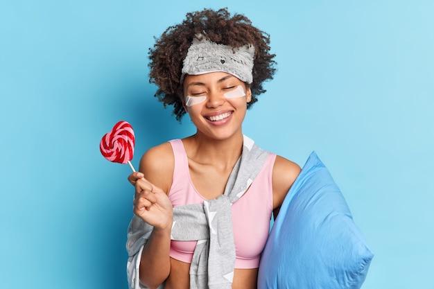 Pozytywna, słodka, kręcona kobieta uśmiecha się szeroko, lubi relaksujące poranne rutyny, ma zdrowe długie pozycje do snu z pozami lizaka w piżamie z poduszką w pomieszczeniu izolowanym nad niebieską ścianą