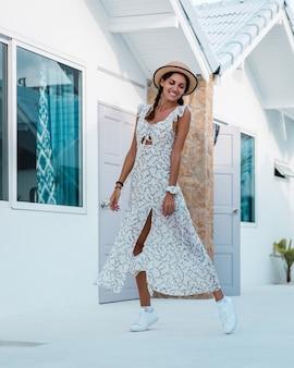 Pozytywna spokojna kobieta w lekkiej letniej sukience, słomkowym kapeluszu, tropikalna lokalizacja