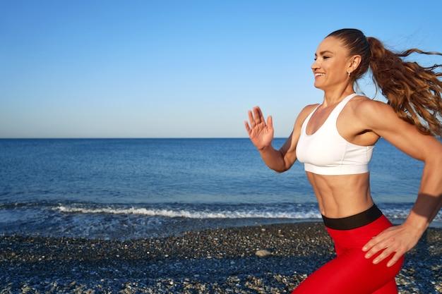Pozytywna, sprawna kobieta na letnim porannym joggingu na plaży w czerwonych leginsach na tle wybrzeża zamknij uo