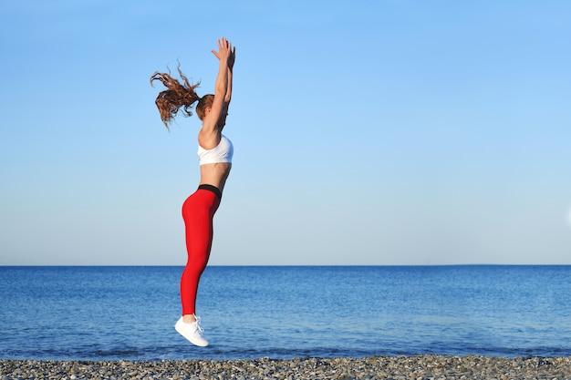 Pozytywna, sprawna kobieta na letnim porannym treningu na plaży w czerwonych legginsach, trening na tle wybrzeża morza, skacząca dziewczyna sportowca
