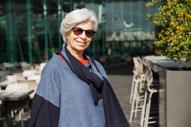 Pozytywna starsza dama pozuje przeciw plenerowej kawiarni