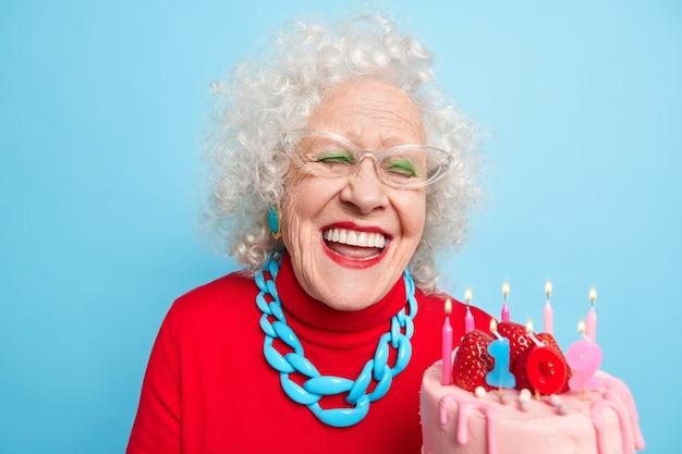 Pozytywna starsza kobieta z siwymi, kręconymi włosami, uśmiecha się szeroko, ma białe, idealne zęby, trzyma ciasto, świętuje urodziny, ma wiek emerytalny