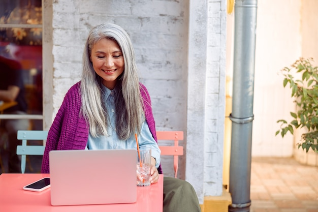 Pozytywna starsza kobieta ze szkłem i smartfonem patrzy na ekran laptopa na tarasie kawiarni na świeżym powietrzu