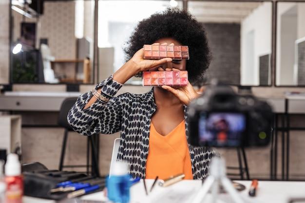 Pozytywna stylistka. piękna modelka o ciemnej karnacji z kręconymi włosami jest zachwycona podczas demonstrowania nowych kolorów szminki