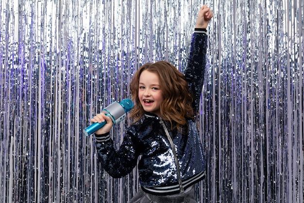 Pozytywna stylowa dziewczyna śpiewa z mikrofonem w dłoniach i uniesioną dłonią na błyszczącej świecidełku