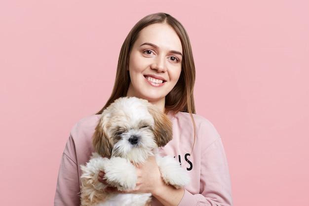 Pozytywna suczka o długich włosach i zadowolonym wyrazie twarzy trzyma swojego ulubionego małego szczeniaczka, izolowanego na różowej ścianie. szczęśliwa kobieta ze zwierzakiem, mają dobre relacje. koncepcja ludzi i zwierząt