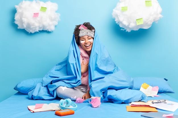 Pozytywna, szczera ciemnoskóra kobieta śmieje się radośnie cieszy się spokojną domową atmosferą owinięta w ciepły koc na wygodnym łóżku otoczona naklejkami na notatnik z pisemnymi pomysłami, co robić