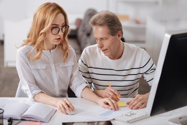 Pozytywna, szczęśliwa dojrzała menadżerka siedzi w biurze i pracuje nad projektem, flirtuje i patrzy na piersi młodej sekretarki