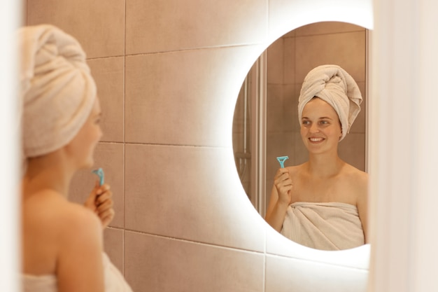 Pozytywna szczęśliwa kobieta trzyma w ręku brzytwę do golenia pod pachami, pozuje w łazience przed lustrem, wykonuje zabiegi higieniczne z dobrym nastrojem i uśmiechem.