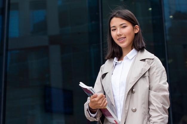 Pozytywna szczęśliwa młoda azjatykcia dziewczyna uśmiechnięta i patrzeje prosto przy kamerą outside