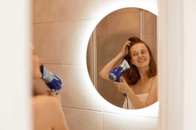 Pozytywna szczęśliwa młoda dorosła kobieta susząca włosy w łazience, trzymająca w rękach suszarkę do włosów, patrząca uśmiechając się na odbicie w lustrze, poranne procedury po wzięciu prysznica.