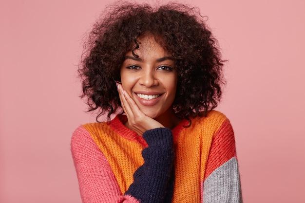 Pozytywna szczęśliwa zadowolona urocza afroamerykanka z fryzurą afro wygląda z przyjemnością, dotyka jej twarzy dłonią, uśmiecha się, nosi kolorowy longsleeve, na białym tle