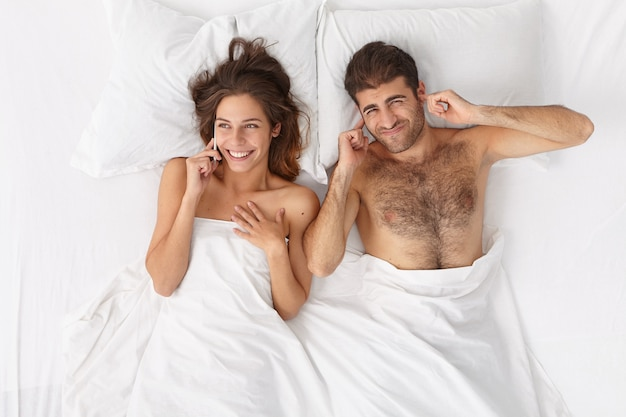 Pozytywna szczęśliwa żona lubi rozmowy telefoniczne, plotki z przyjaciółką podczas leżenia w łóżku, zirytowany mąż leży blisko i zatyka uszy. kobieta przerywa mężczyźnie spanie, głośno rozmawia przez telefon komórkowy