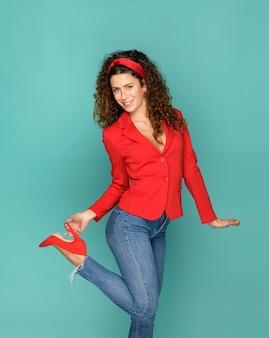 Pozytywna szczupła kobieta w stylowym stroju, uśmiechając się do kamery i dotykając pięty czerwonego buta na turkusowym tle