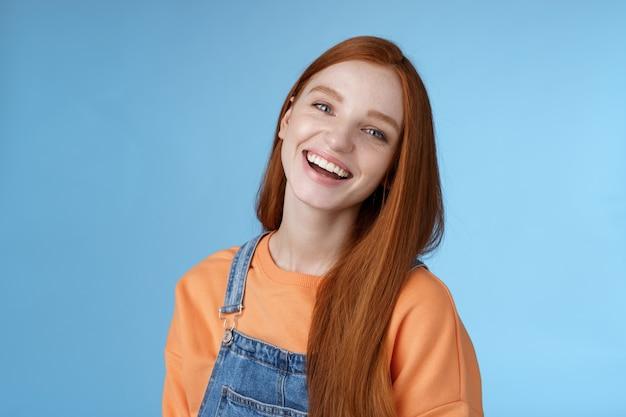 Pozytywna towarzyska, żywa ruda dziewczyna śmieje się radośnie dobrze się bawi rozmawia przyjaźni przyjaciele przechylanie głowy chichocze żarty śmieszne momenty z życia stojące pozytywne szczęście niebieskie tło pomarańczowa koszulka
