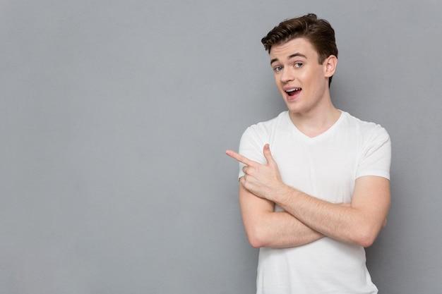 Pozytywna treść szczęśliwy uśmiechnięty pewny siebie młody człowiek w białej koszulce wskazujący w copyspace