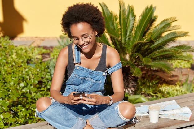 Pozytywna turystka używa współczesnych telefonów komórkowych do wysyłania wiadomości w sieciach społecznościowych, trzyma skrzyżowane nogi, nosi okulary i dżinsowe ogrodniczki, lubi wakacje w tropikach, kawę i mapę w pobliżu