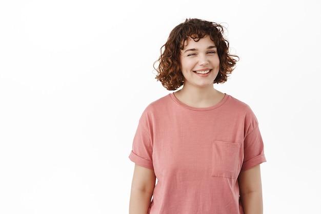 Pozytywna urocza dziewczyna, mruga do ciebie i uśmiecha się, pokazuje idealny uśmiech z białymi zębami, sugerując coś ciekawego, stojąc szczęśliwie na białym.