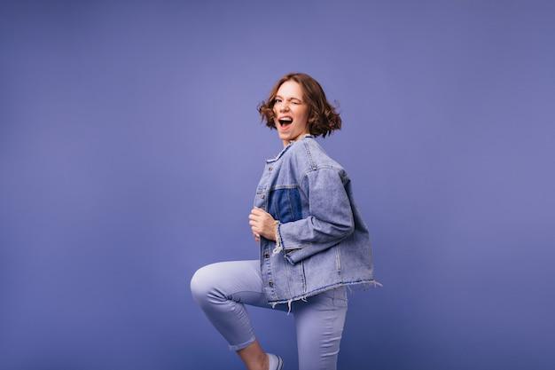 Pozytywna urocza kobieta skacze i śmia się. sympatyczna modelka w oversize'owej dżinsowej kurtce do tańca.