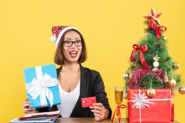 Pozytywna urocza pani w garniturze z czapką świętego mikołaja i okularami pokazująca prezent i kartę bankową w biurze na żółto na białym tle
