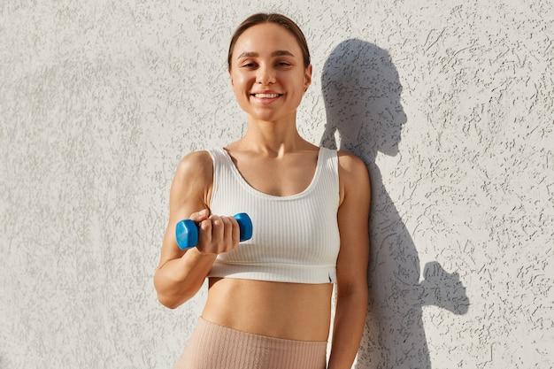 Pozytywna uśmiechnięta kobieta o ciemnych włosach, ubrana w biały sportowy top stojący na białym tle na zewnątrz, trzymając w ręku niebieski hantle, trenując biceps.