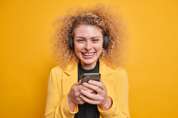 Pozytywna uśmiechnięta młoda kędzierzawa kobieta trzyma telefon komórkowy sprawdza skrzynkę e-mail będąc w dobrym nastroju słucha muzyki przez słuchawki, ubrana formalnie, cieszy się wolnym czasem na białym tle nad żywą żółtą ścianą