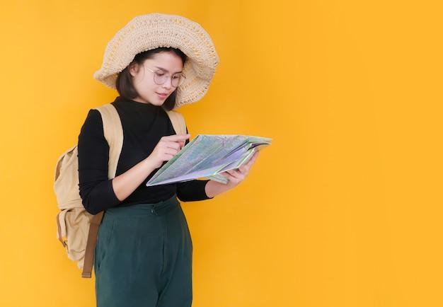 Pozytywna, uśmiechnięta młoda turystka szuka inspirujących miejsc i trzyma papierową mapę